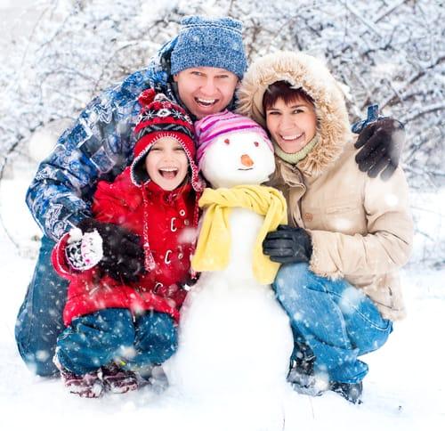 divertirsi d'inverno all'aperto con la famiglia il pupazzo di neve